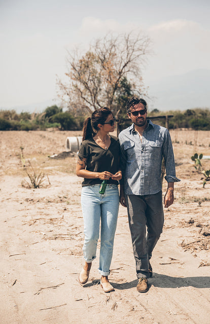 A couple talking and walking through a dry field.