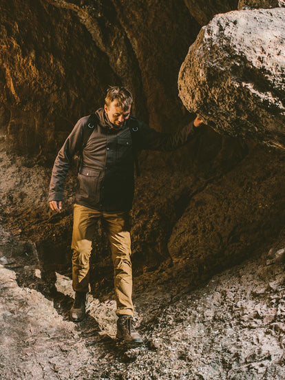 Hiking through a cavern wearing The Hawkins Jacket.