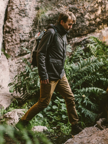 Our guy wearing The Hawkins Jacket, hiking over some rocky vegetated terrain.