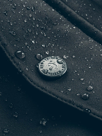 Close up of a TS-branded press stud fastener on The Hawkins Jacket.