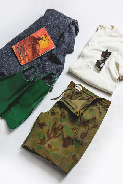 A flatlay of an outfit, including our The Adventure Short in Arid Camo, alongside some outdoor gear.