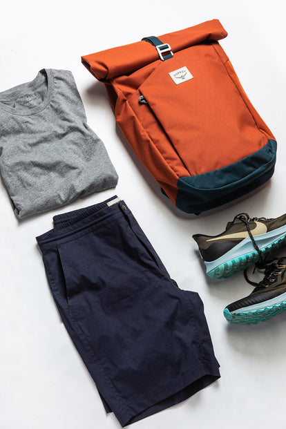 A flatlay of an outfit, including our The Adventure Short in Navy, with a backpack and hiking shoes.