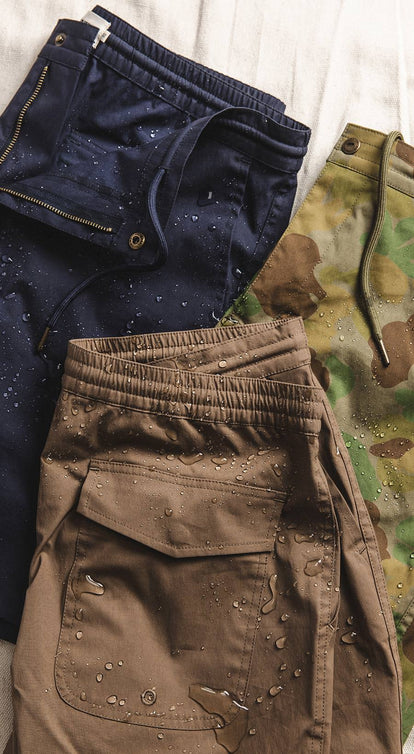 Flat lay of our three Adventure Shorts, folded neatly with some outdoor gear.