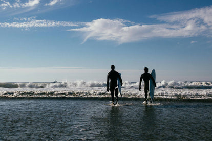 Two surfers walking out into the surf, boards under arms