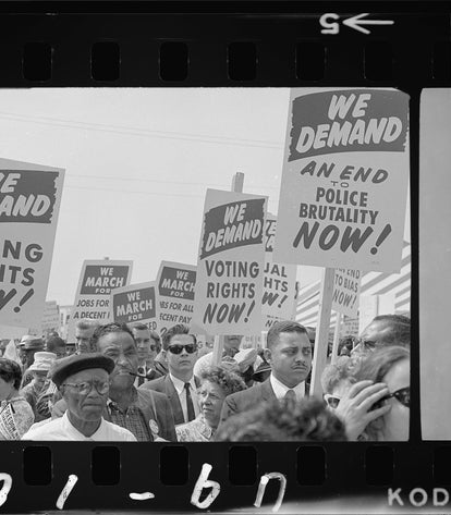 A black and white still from a film reel, showing a crowd of men and women marching with voting rights plackards.
