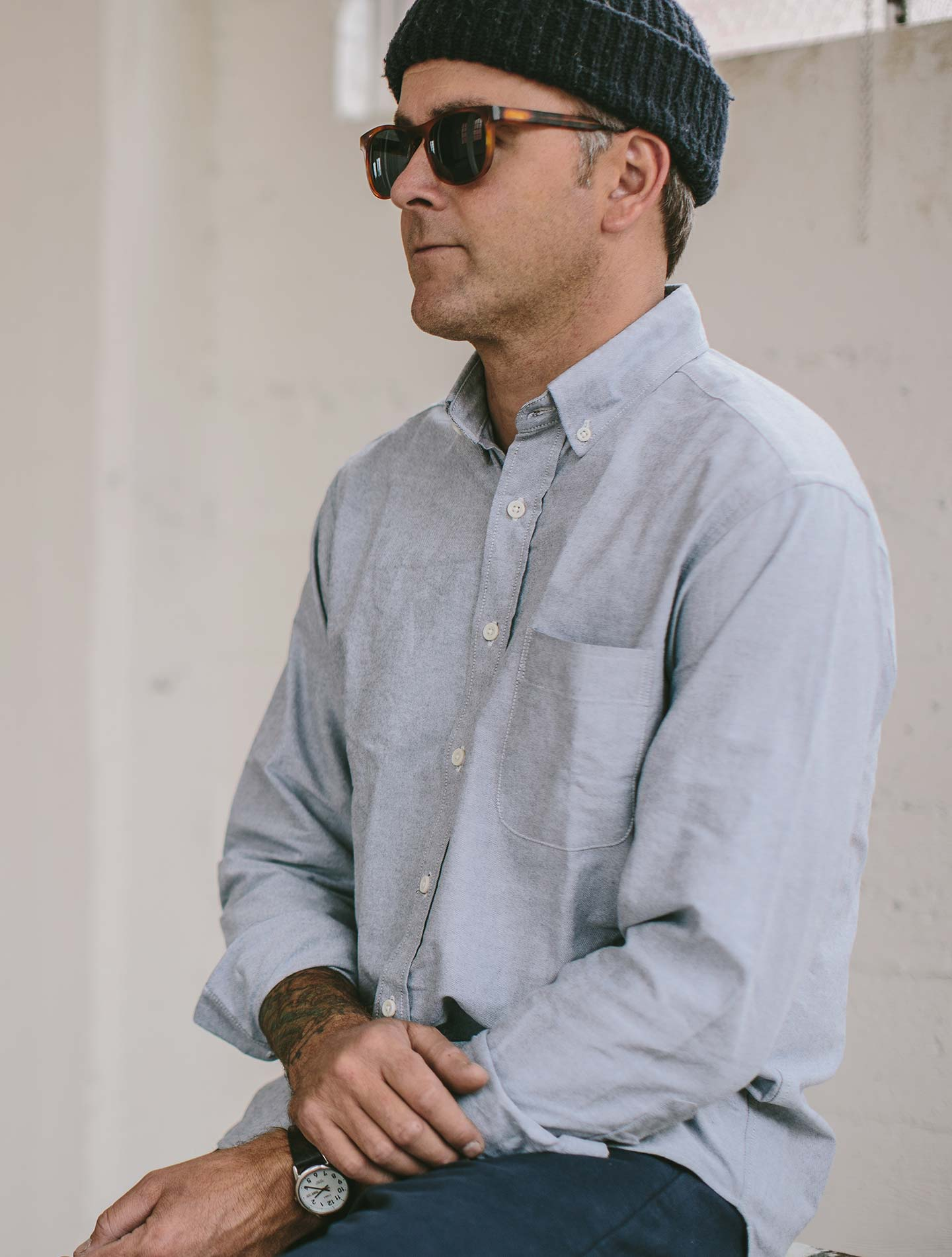 A blind man in a beanie, wearing a blue Taylor Stitch oxford.