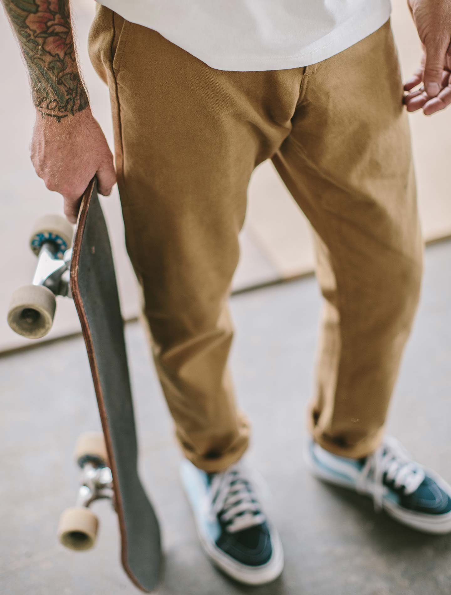 A dude with a skateboard, wearing chinos.