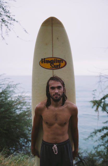 A surfer posing with his
