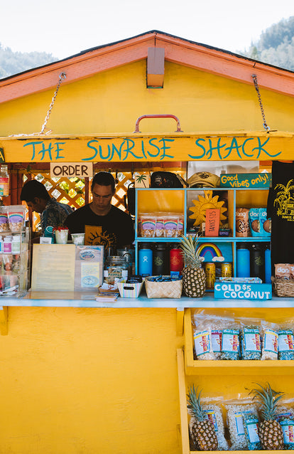 Staff at yellow-painted wooden counter, topped with pineapples; The Sunrise Shack.