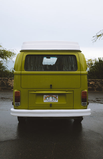 Rear view of a nicely painted green vintage VW bus.