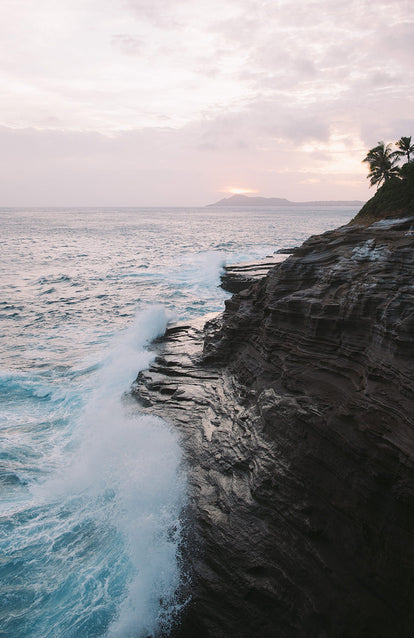 A coastal cliff with breaking waves and a cloudy sunset over some distant palm-topped islands.
