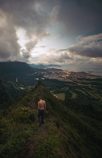 A shirtless hiker descending an edge-of-town trail, lights from the buildings illuminating the coastal scene.