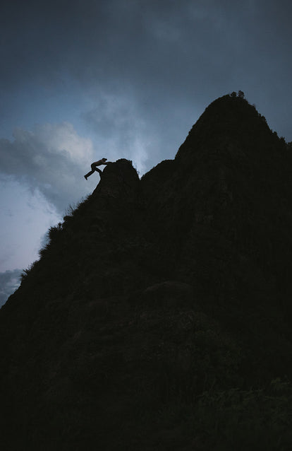 A sillhouetted climber swinging out over the top of a boulder, on a ridge, at dusk.
