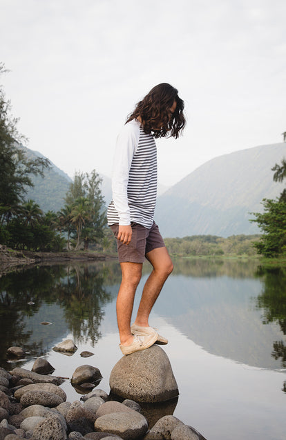 A long-haired guy cleanly and crisply dressed in shorts and Henley, balancing on a small rock on the edge of a small glassy tree-lined lake.
