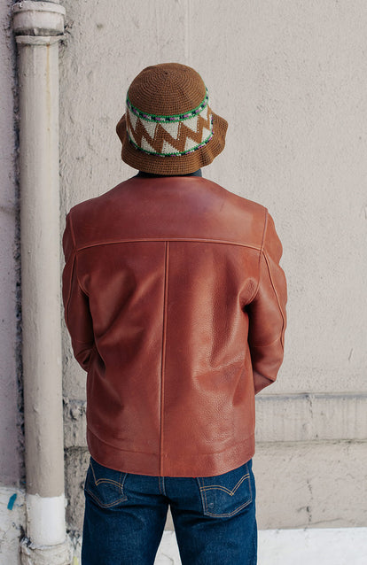 Rear view of a man wearing a brown leather jacket.