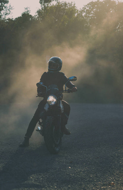 A faded front-on shot of a man on a motorcycle, stopped with one leg on the ground, out to the side.