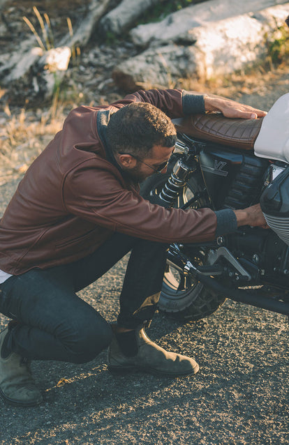 Making some adjustments to the engine on a motorcycle, wearing a brown leather jacket.