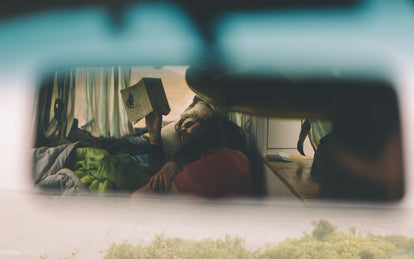 Shot through the rearview mirror of someone reading a book, lying in the back of a campervan.