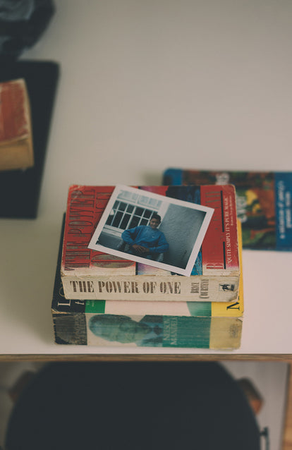 Polaroid of an African teen, on top of two novels about Nelson Mandela.