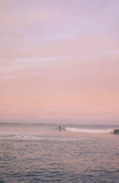 Surfing some small glassy waves, with the pink sky reflected.