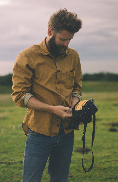 A bearded photographer changing the folm in his SLR.