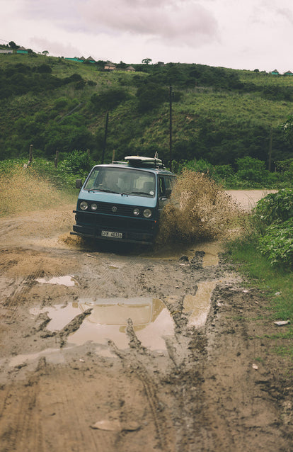 A VW camper fording a muddy creek.