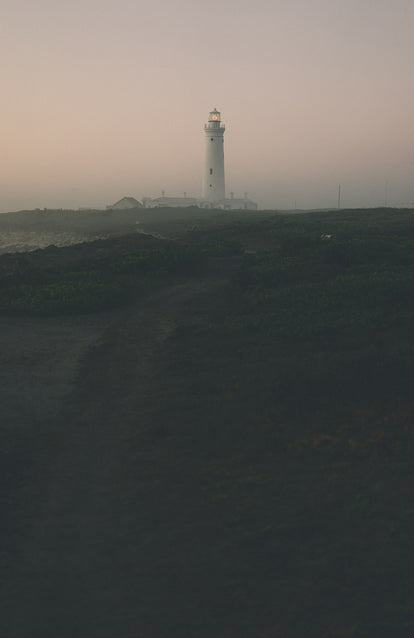 A lighthouse and connected buildings across a foggy shoreline at dusk.