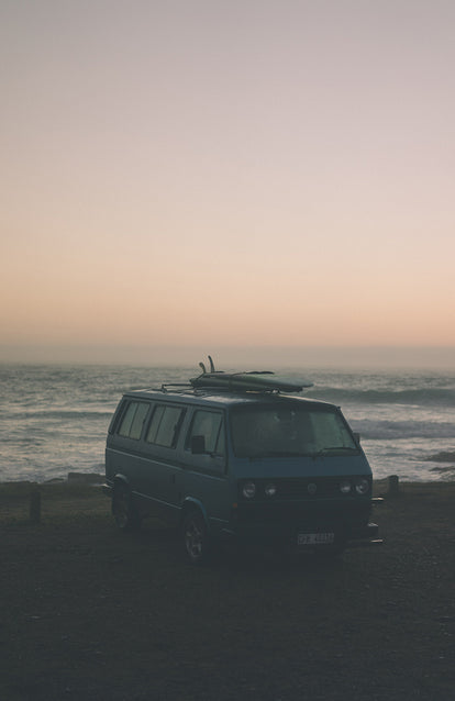 Campervan parked up in a misty oceanside spot.