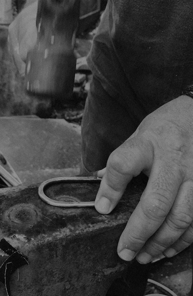 black and white image of billy working on his boots and belts