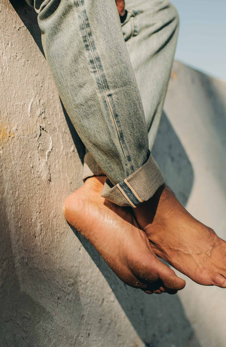 our fit model wearing the 24 month wash denim on the beach—cuffed selvage shot