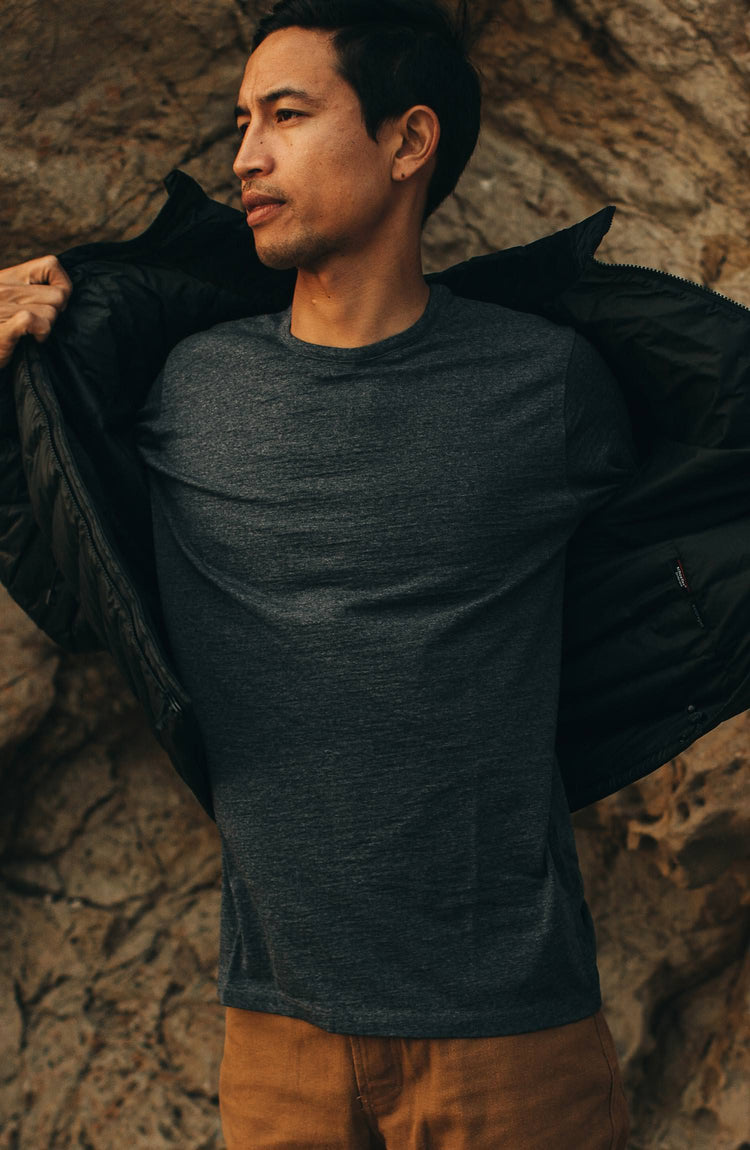 our guy rocking the merino tee near a cliff—split shot