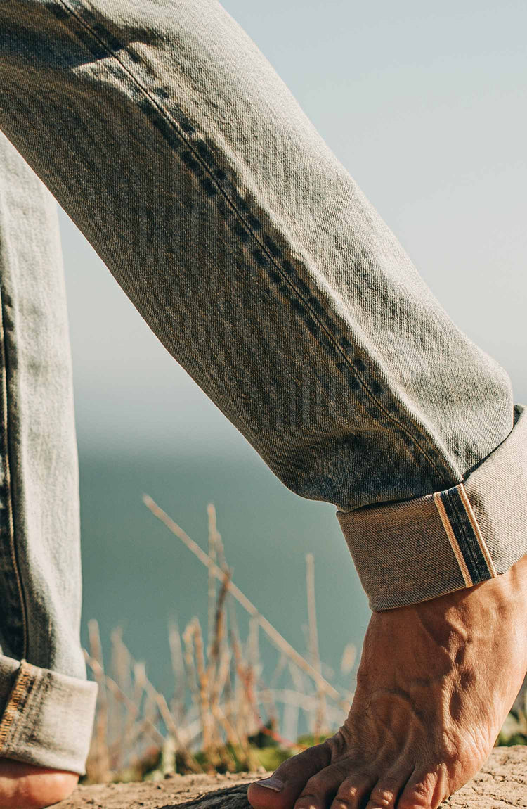 our fit model wearing the 24 month wash denim on the beach—cropped shot of legs
