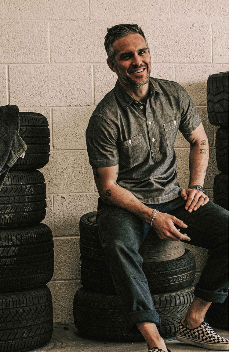 The Short Sleeve Popover in Charcoal Chambray — Model wearing shirt in the garage