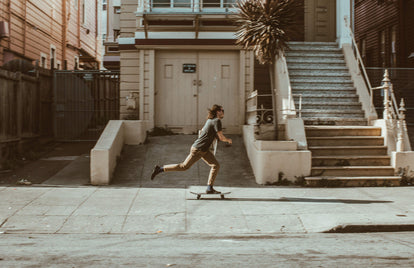 Skateboarder, pushing through the city streets.