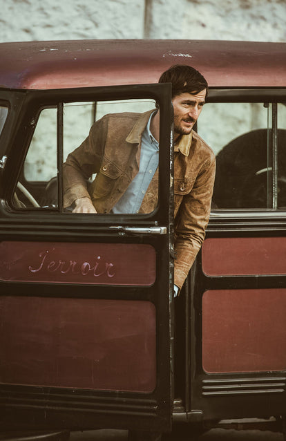 Exiting a wood-panelled vehicle in a nice Long Haul Jacket and crisp Blue Oxford.