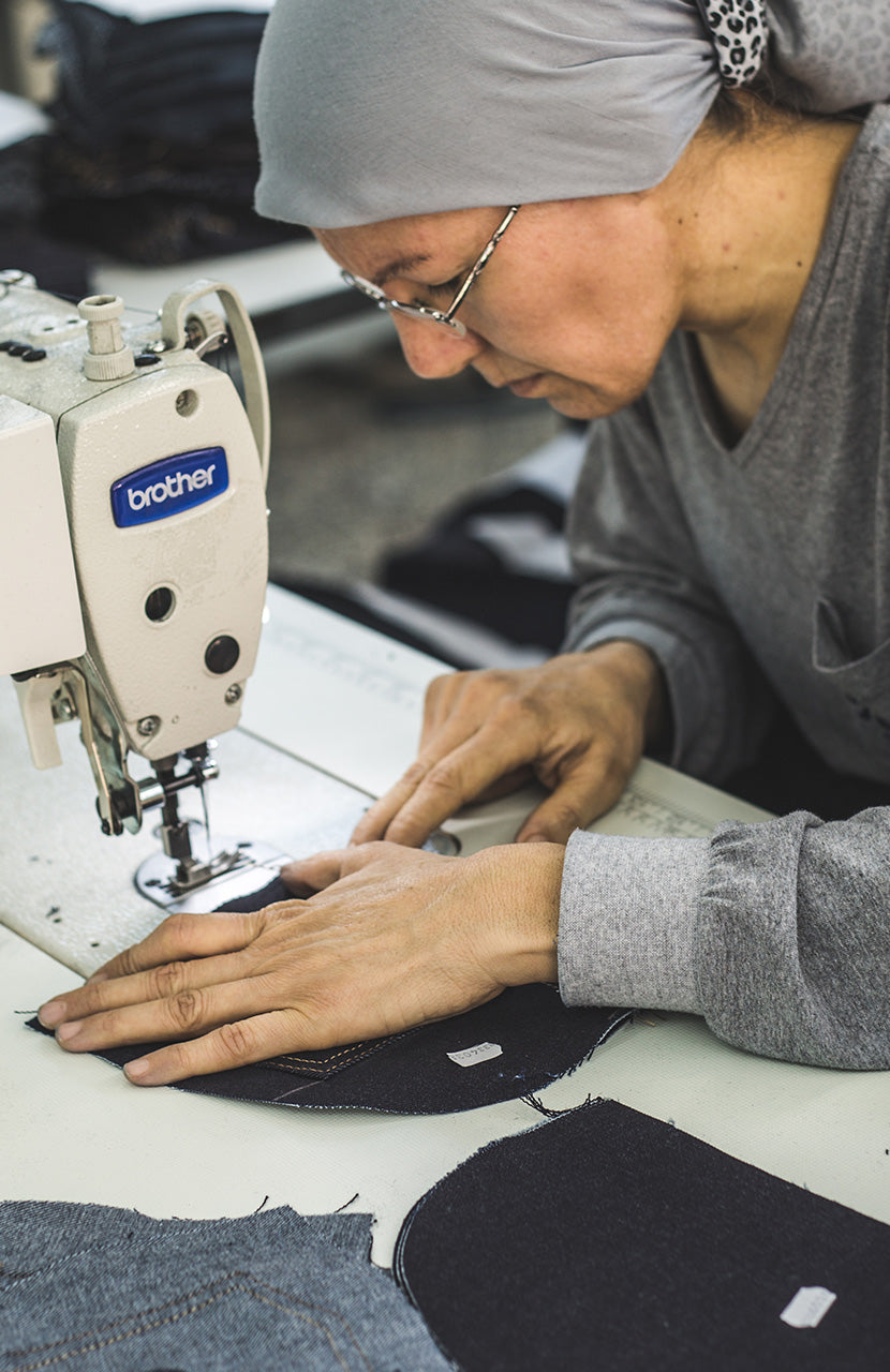 A woman aptly sews denim pieces into place.