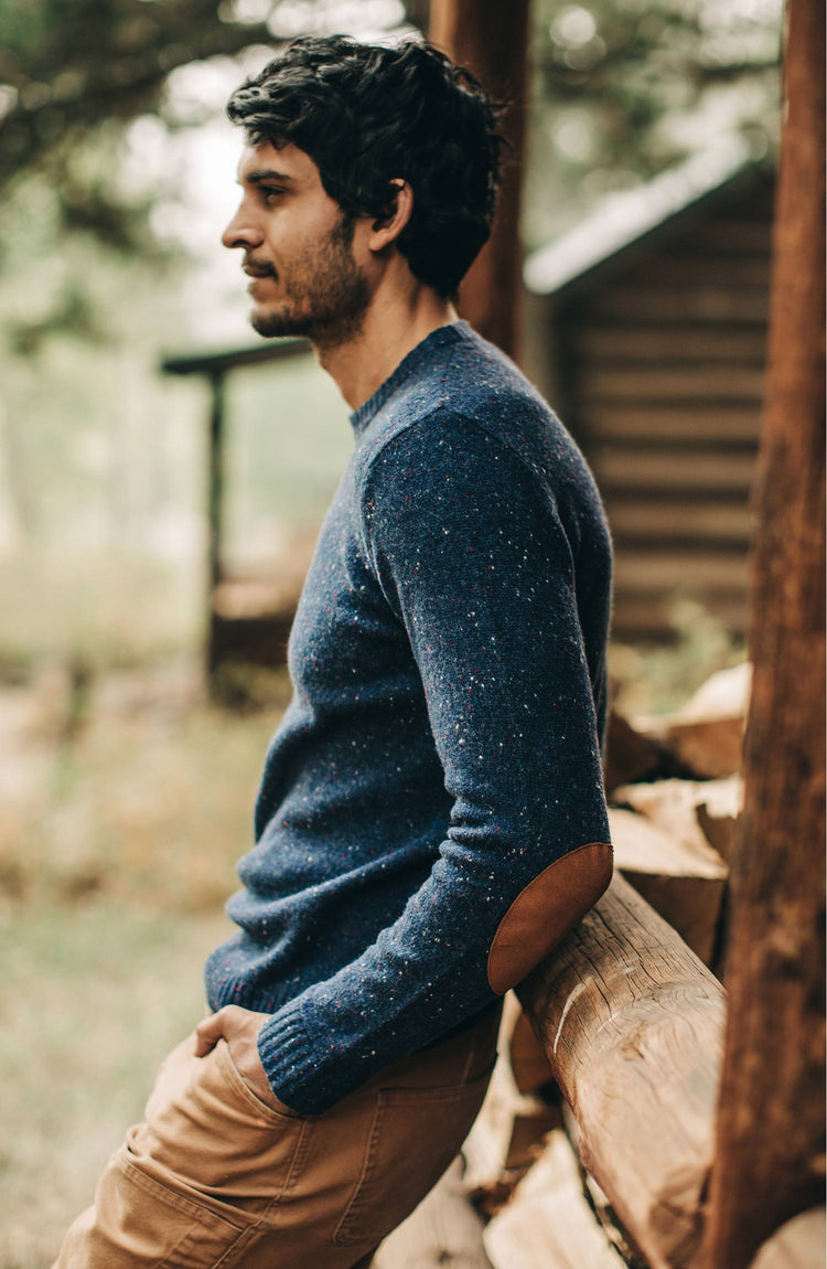 The Hardtack Sweater in Navy Donegal — Model from the left leaning up against cabin