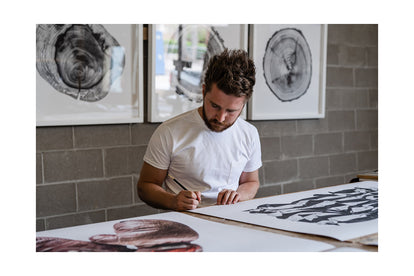 Jack Ludlam signing a print of the American Flag in his studio