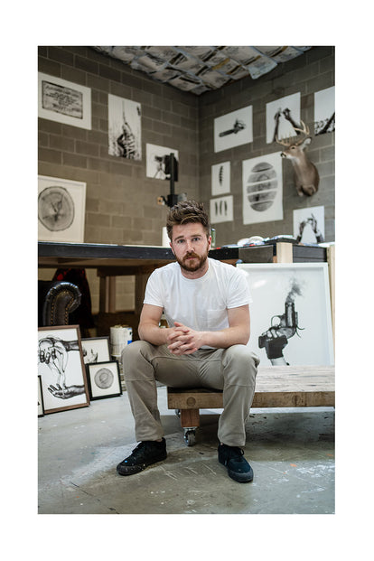 Jack Ludlam posing in his photography studio with prints surrounding him