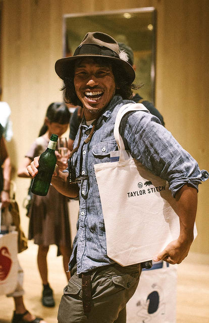 A guy wearing a hat and denim shirt, laughing, holding a beer and toting a TS bag.