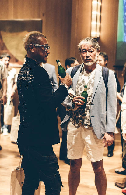 Two fashionable guys, drinking beer, with other people socializing in the same room.