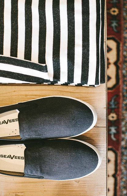 A pair of SeaVees-branded slip-on shoes and a white-striped shirt folded next to them.