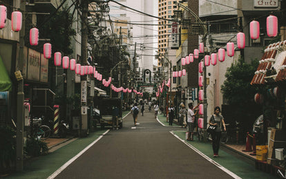 A relatively empty city street festooned with pink and white striped paper lanterns.