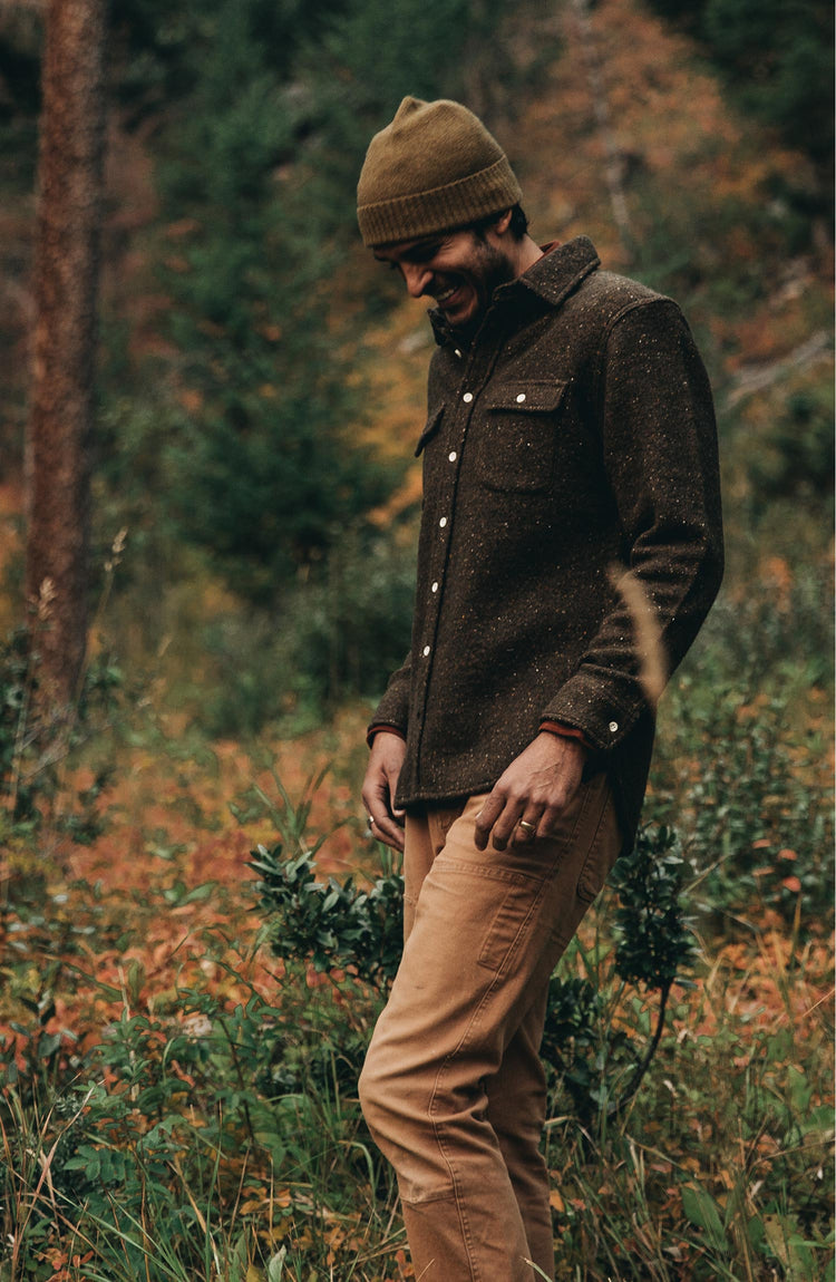 our guy wearing The Leeward Shirt in Olive Donegal from the front in a field of wildflowers