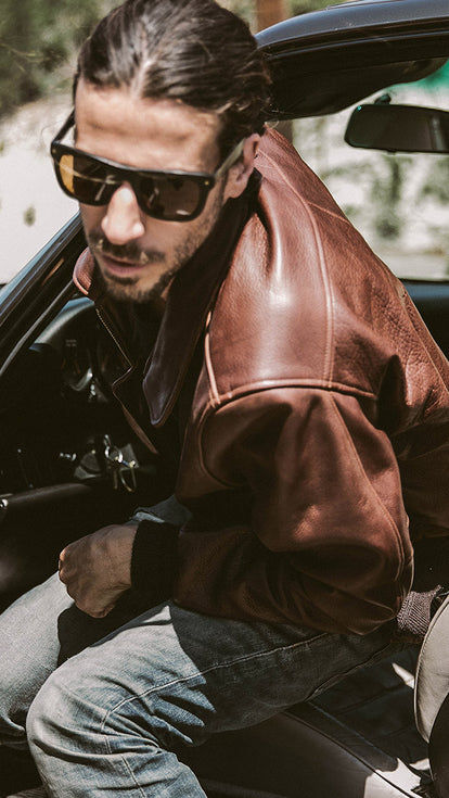 Our guy climbing out of a car, wearing sunglasses and a leather jacket.