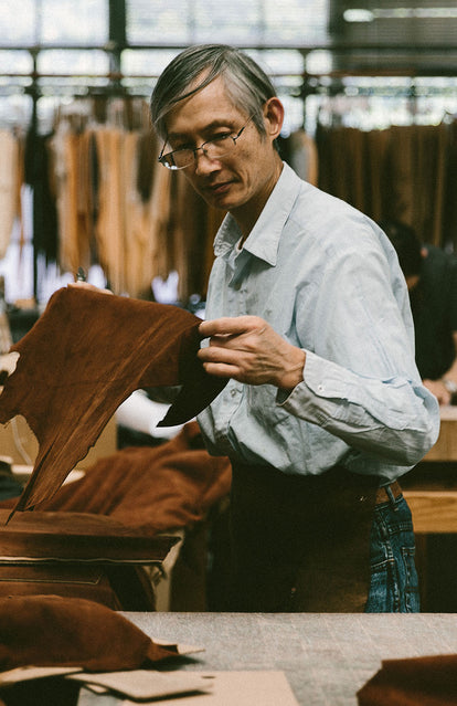 A spectacled man inspecting a suede panel, with lots of leather hanging on a rack in the background.