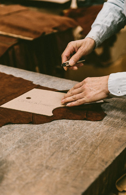 Close up on hands cutting a pattern out of a suede panel with a razor knife.