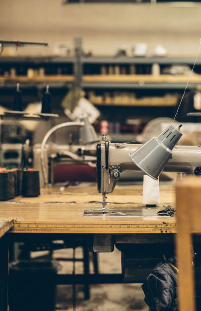 A sewing machine and desk lamp on a table within a workshop.