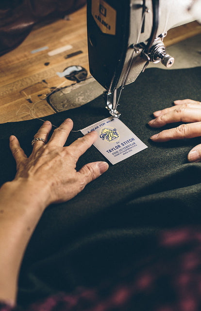 Close up on a woman stitching the label on a TS x Golden Bear jacket lining.