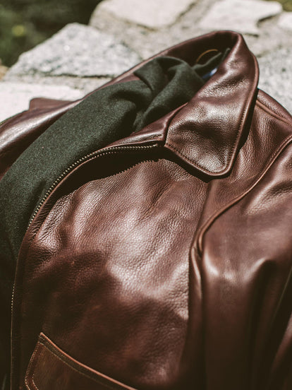 Close-up shot of a leather jacket folded up with a green scarf inside.